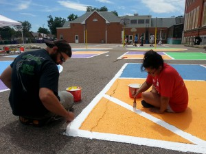 teacher and student painting on playground